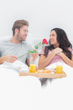 Handsome man giving a rose to his wife during breakfast in their bed photo