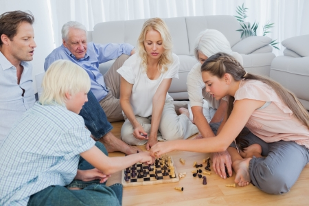 jugando ajedrez: Familia extensa jugando al ajedrez en la sala de estar