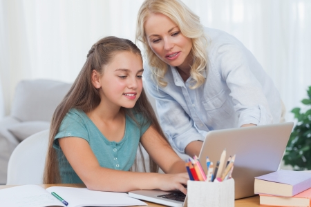 deberes: Madre ayudando a su hija a hacer la tarea con un ordenador port�til Foto de archivo