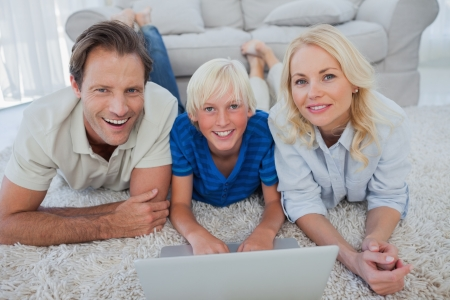 Portrait of son and parents using a laptop lying on a carpet photo