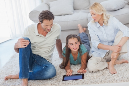 Young girl and her parents using a tablet lying on a carpet photo