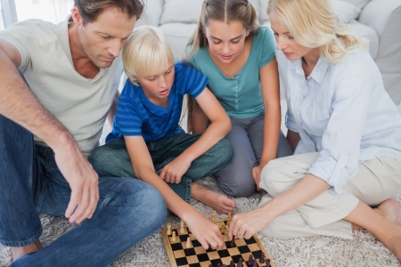 Portrait of a cute family playing chess lying on a carpet photo