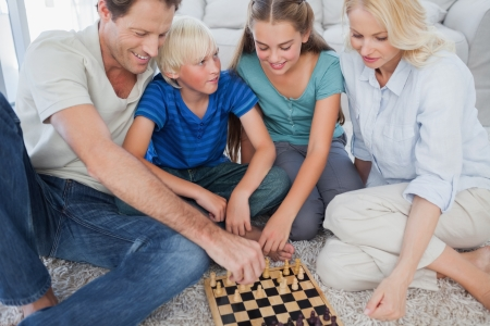 Portrait of a cheerful family playing chess lying on a carpet Stock Photo - 20640378