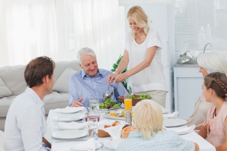 Woman serving salad to grandfather at the dinner table photo