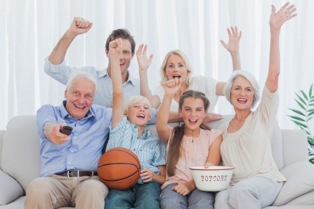 boy basketball: Extended family watching the tv on sofa Stock Photo