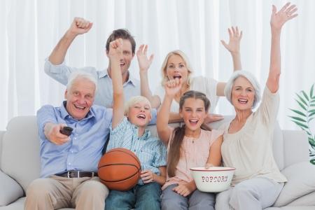 baloncesto chica: Familia extensa viendo la televisi�n en el sof�