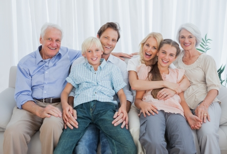 Portrait of an extended family sitting on couch and smiling at camera photo