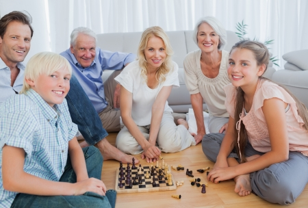 Happy family looking at the camera and playing chess photo