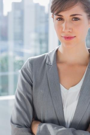 Beautiful businesswoman smiling at camera beside large window