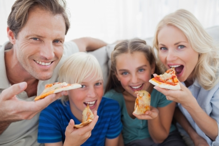 Smiling family eating pizza and looking at camera photo