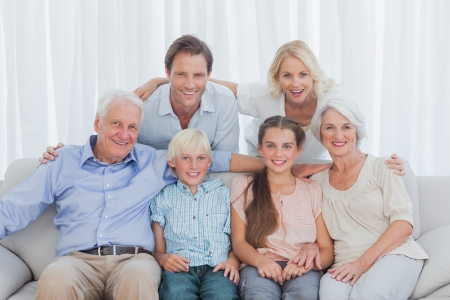 Extended family sitting together on couch smiling at camera Stock Photo - 20668327