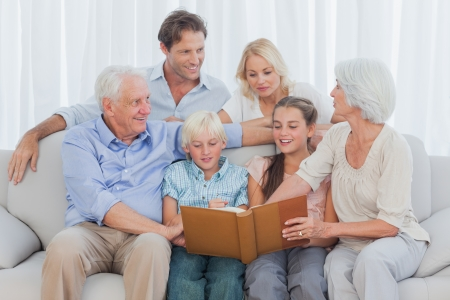 Extended cheerful family looking at a photo album in living room Stock Photo - 20639285