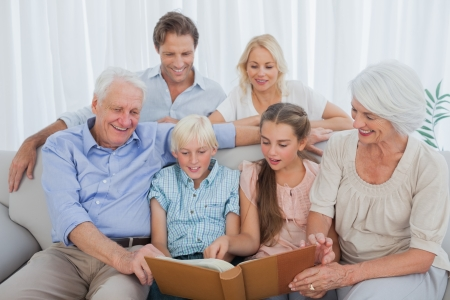 Extended family looking at an album photo in the living room Stock Photo - 20638794