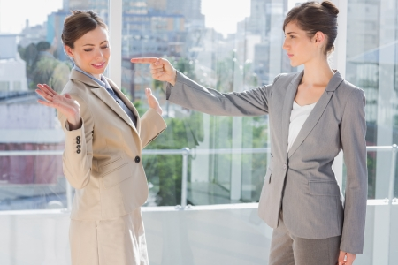rival: Angry businesswoman pointing at her rival in a bright office