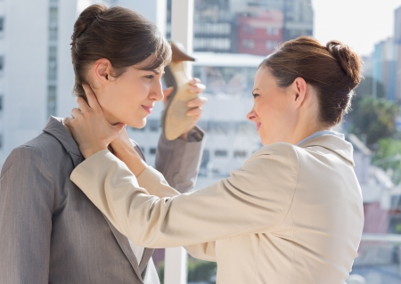 strangling: Businesswoman strangling another in the office Stock Photo