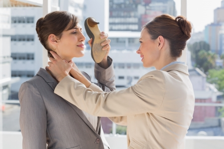Businesswoman strangling another who is defending with her shoe in bright office photo