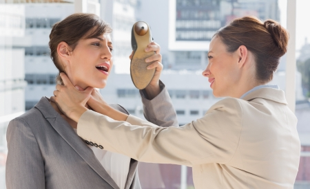 violence in the workplace: Businesswoman defending herself from her colleague strangling her in a bright office Stock Photo