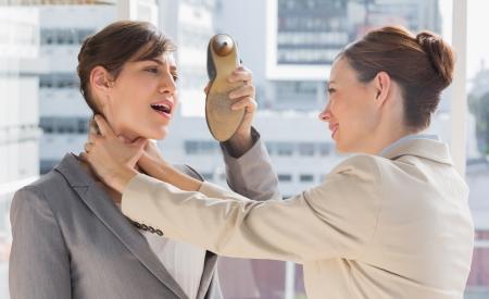 violence in the workplace: Empresaria defenderse de su colega estrangularla en una oficina brillante Foto de archivo