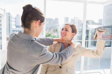 violence in the workplace: Businesswoman strangling her partner holding a shoe in bright office