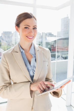 Happy businesswoman using her tablet pc and looking at camera photo