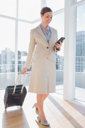 tied down: Businesswoman pulling her suitcase and checking her phone in bright office Stock Photo