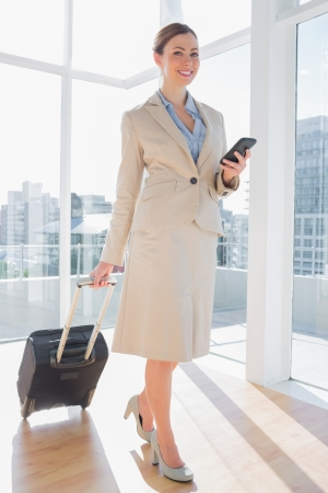 Businesswoman walking with suitcase and checking her phone in large bright office photo