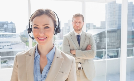 Call centre agent standing with colleague behind her in bright office photo