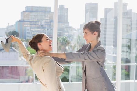 Businesswomen having a massive fight in a bright office photo