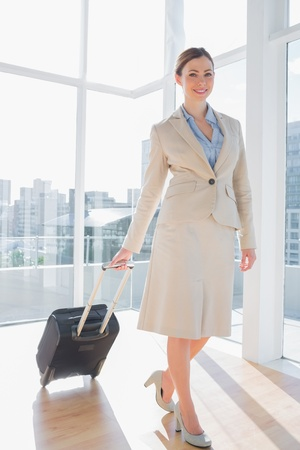Businesswoman pulling her suitcase and smiling at camera in birhgt office photo