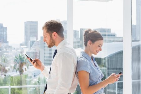 well dressed  holding: Business team standing back to back and texting in a bright office Stock Photo