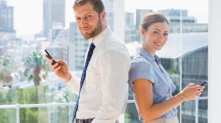 Smiling business team standing back to back and texting in a bright office photo