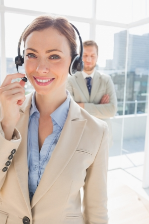 Call centre agent smiling with colleague behind her in bright office photo