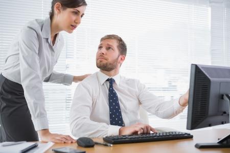 コンピューターのオフィスで彼の机で彼の同僚の何かを見せ実業家