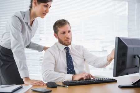 computer office: Businessman showing his colleague something on computer at desk in office
