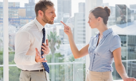 Business partners having a heated argument by large windows photo