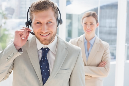 Handsome call centre agent with colleague behind him in a bright office photo