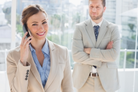 well dressed  holding: Happy businesswoman having phone conversation with colleague behind her