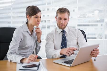 Les gens d'affaires travaillant ensemble sur un ordinateur portable au bureau à bureau