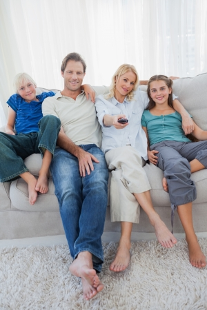 Portrait of a family watching television sitting on a couch photo