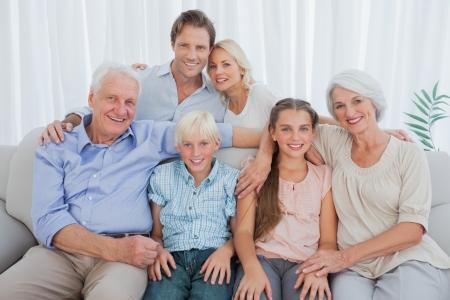 retrato: Familia extensa que se sienta en el sofá y sonriendo a la cámara
