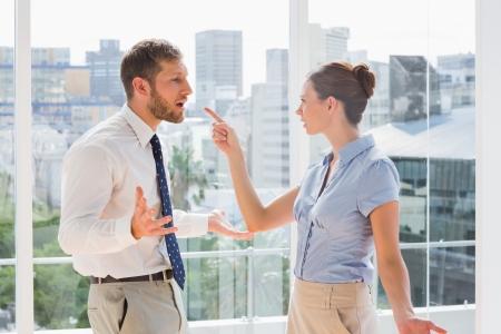 personas discutiendo: Equipo de negocio tener una acalorada discusi�n en una oficina brillante