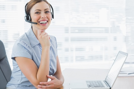 Laughing call centre agent wearing headset at her desk with laptop in office photo