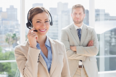 Happy call centre agent with colleague standing behind her in office photo