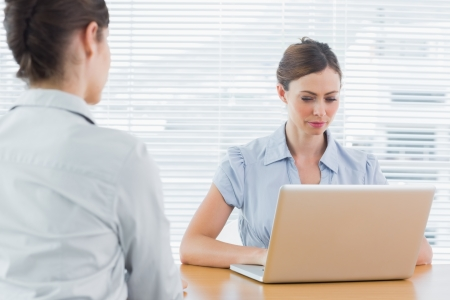 Businesswoman looking at laptop during an interview at desk in office photo