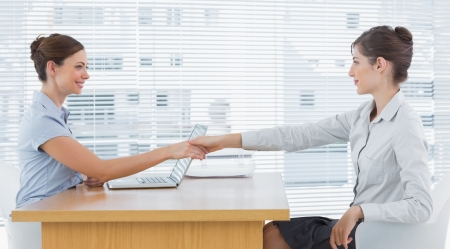 agreeing: Businesswoman shaking hands with interviewee at desk in office