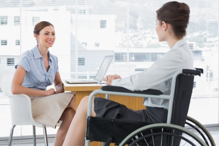 Businesswoman speaking with disabled colleague at desk in office photo