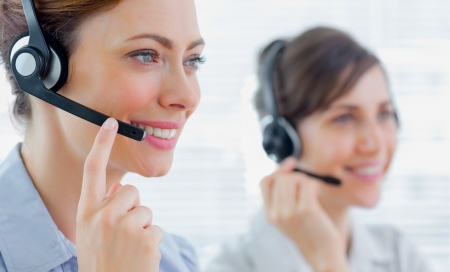 call: Call centre agents with headsets at work smiling  Stock Photo