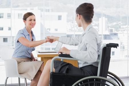 personas discapacitadas: Empresaria que sacude las manos con su colega discapacitado en el escritorio en la oficina