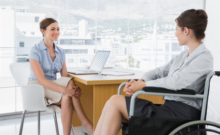 Businesswoman chatting with disabled colleague at desk in office photo