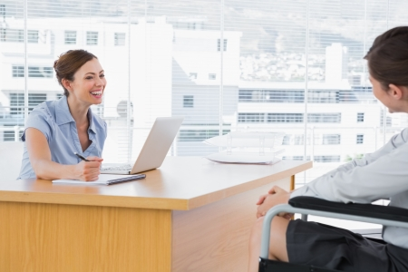 equal opportunity: Businesswoman smiling at disabled job candidate in her office at desk